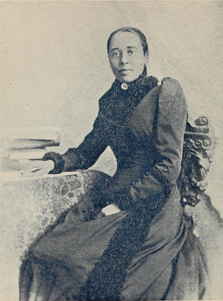 Anna Julia Cooper sits for portrait. Her arm rests next to a pile of books and she holds a pen.