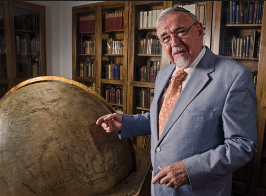 Photograph of Dr. Karl Butzer pointing at an antique globe with wall-to-ceiling grass bookcases in the background