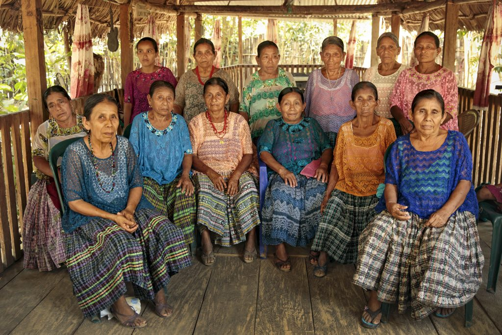 The abuelas [grandmothers] of Sepur Zarco. First row seated (from right-left): Antonia Choc (blue huipil); Felisa Cuc (orange huipil); Rosario Xo (blue huipil); Candelaria Maaz (pink huipil); Manuela Bá (light blue huipil); Demesia Yat (dark blue huipil); Seated behind Demesia Yat (left) (wearing white huipil with green embroidery): Margarita Chub. Standing, second row, (from right-left): Matilde Sub (pink); Catarina Caal (off-white); María Bá (purple huipil); Cecelia Xo (purple huipil); Carmen Xol (tan flowered huipil)