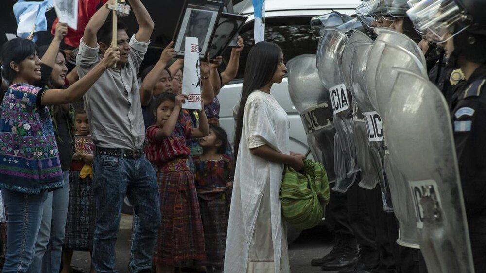 María Mercedes Coroy as Alma walks through protestors toward police in a still from the film.
