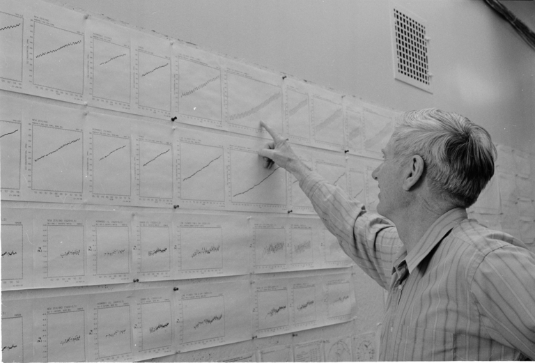 Charles Keeling faces a wall with copies of the Keeling Curve