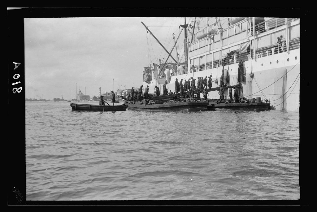 Men, moving from smaller boats, add coal to a steamship in Port Said, Egypt