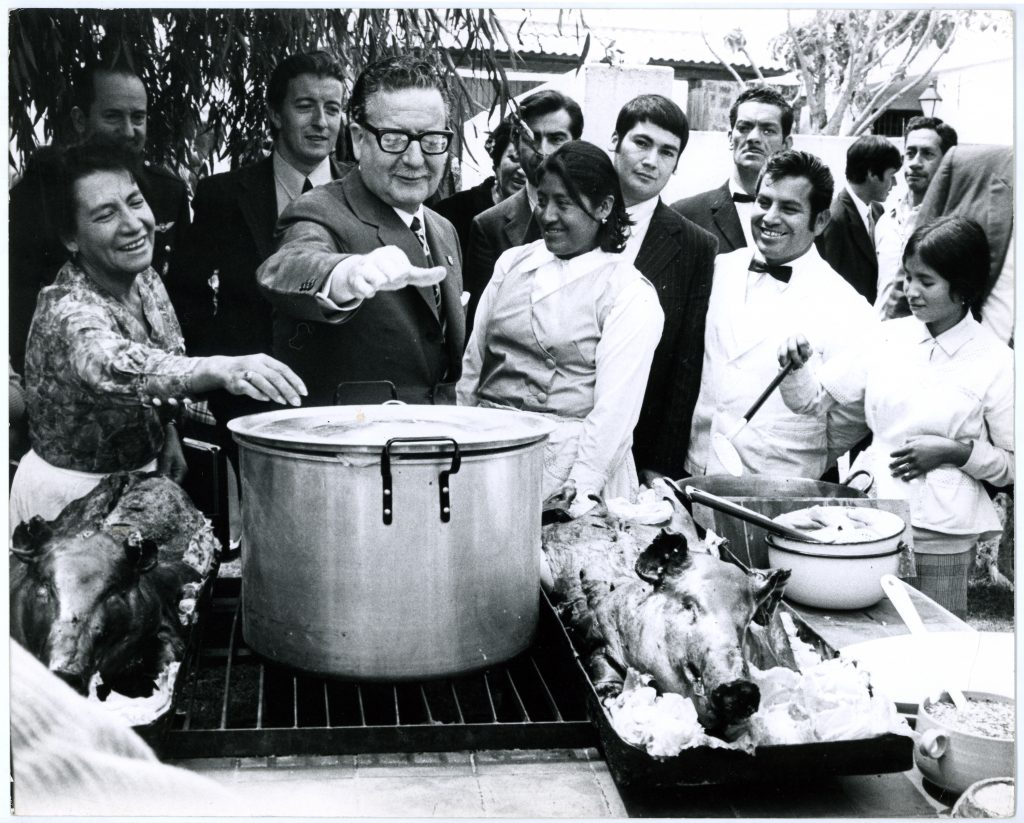 Salvador Allende reaches for the lid of a large soup pot at a community potluck during the UP.