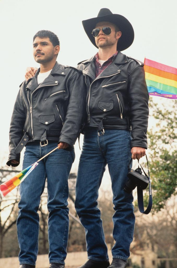 Photograph of two men wearing black leather jackets and jeans at a Gay Pride Event. The man on the left is holding a small rainbow flag and the man on the right is holding a camera and has his arm around the man on the left.