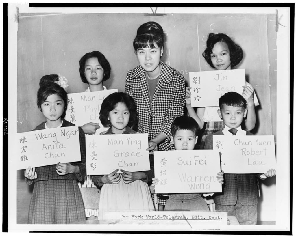 Miss April Lou, a teacher in Manhattan, poses with six Chinese children, recent arrivals from Hong Kong and Formosa, who are holding up placards giving his or her Chinese name (both in ideographs and in transliteration) and the name to be entered upon the official school records.