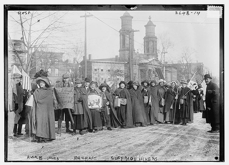 Black and white photograph by Richard Arthur Norton called Suffrage Hikers showing a line of women and men holding protest signs and flags