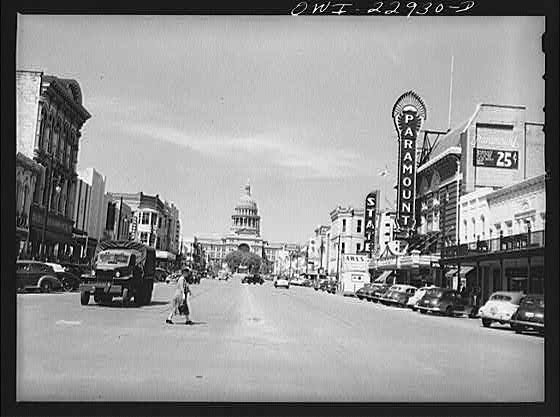Black and white photograph of Congress Avenue in downtown Austin, Texas with a view of the State Capital Building in the background