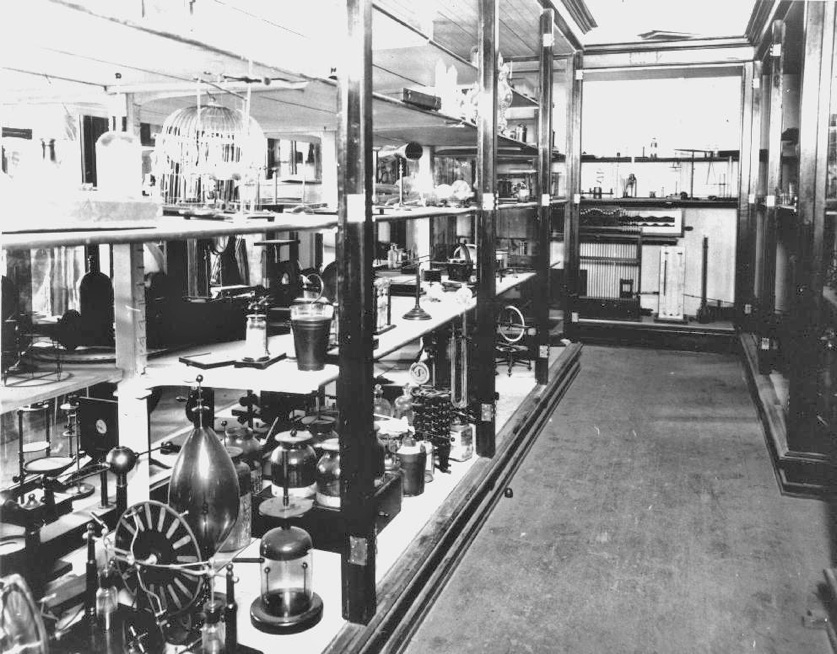 A black and white photograph of the physics department's earliest demo equipment on rows of shelves