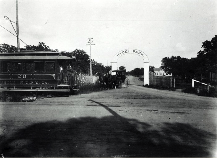 Gated entrance to Hyde Park in Austin, Texas in the 1890s featuring a trolley car to the left of the entrance