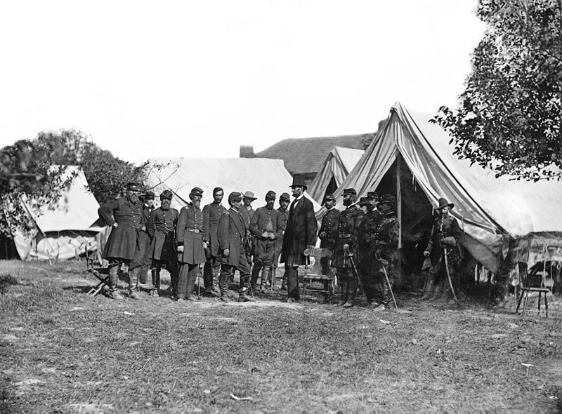 Black and white image of President Abraham Lincoln meeting with Union General McClellan and his officers outside a tent after the Battle of Antietam