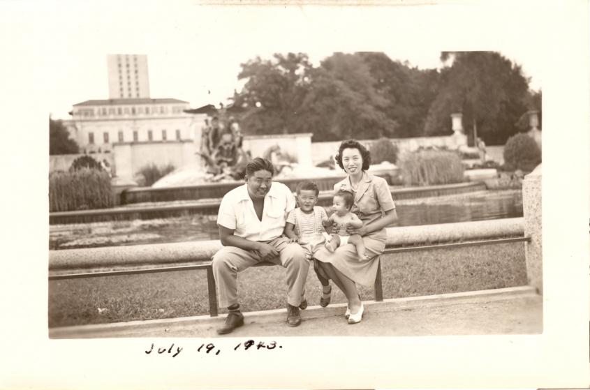 Image of an Asian family from July 19, 1943 sitting on the edge of a fountain on the campus of the University of Texas at Austin
