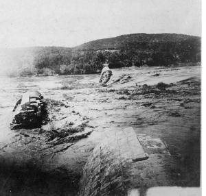 Black and white image of the destroyed Austin Dam with large chunks of debris in the water after the flood of 1900