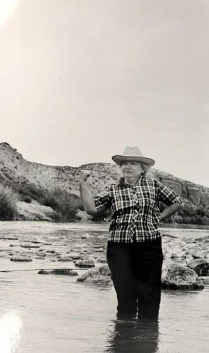 Black and white image of Mary Elizabeth Sutherland Carpenter standing knee-deep in a river with mountains in the background