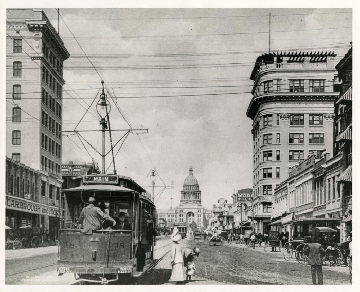 Black and white image of a trolley car moving down Congress Avenue towards the Texas State Capital Building