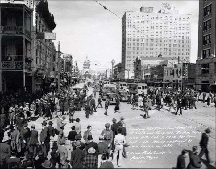 Black and white photograph of large groups of pedestrians crossing Congress Avenue in downtown Austin, Texas